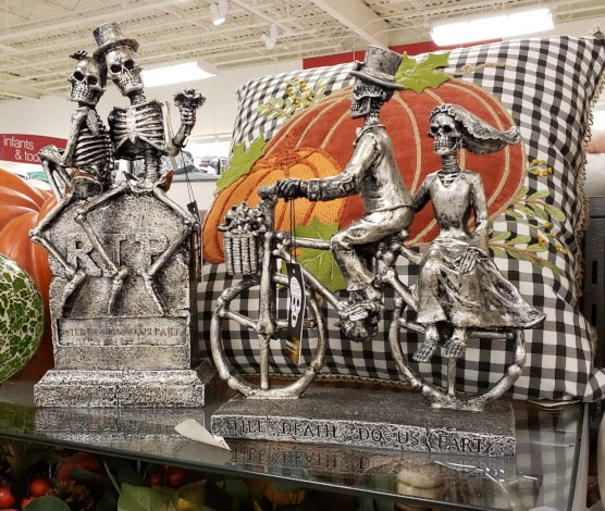 Skeleton couples on a tombstone and on a bike